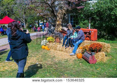 Lancaster PA USA - October 9 2016: Visitors pose for a picture with an old tractor at the Landis Valley Farm and Museum during the annual Harvest Day event.
