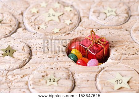 Advent calendar handmade from old timber with open window. Circular space filled with small gift and jelly beans. Calendar to count the days before Christmas. Medieval wood with wormholes. Macro photo