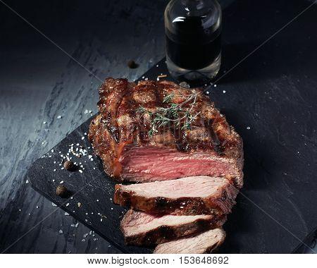 Closeup of cut medium rare roast beef steak with herbs and bottle of sauce