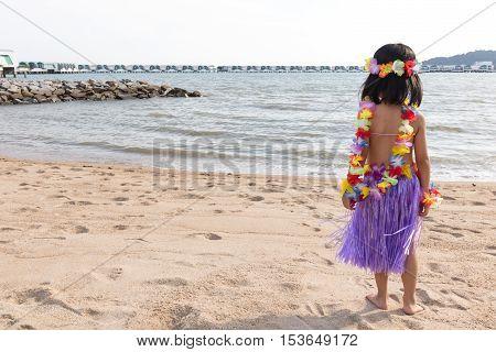 Asian Chinese Little Girl In Hawaiian Costume Looks Far Away