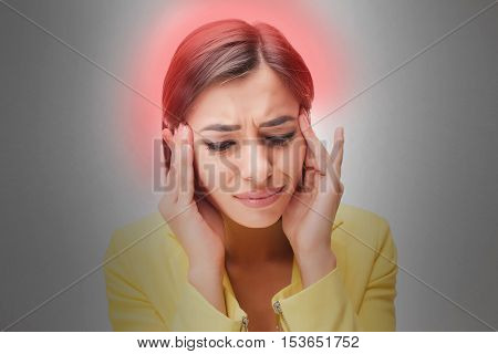 The young woman's portrait with pain emotions on gray background. Concept headache