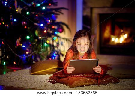 Adorable Little Girl Using A Tablet Pc By A Fireplace On Christmas Evening