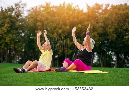 Senior couple does yoga. People sitting on mats outdoors. New hobby of grandparents. Good health and peaceful mind.