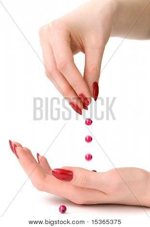 Droping bead. Woman hands isolated on white.