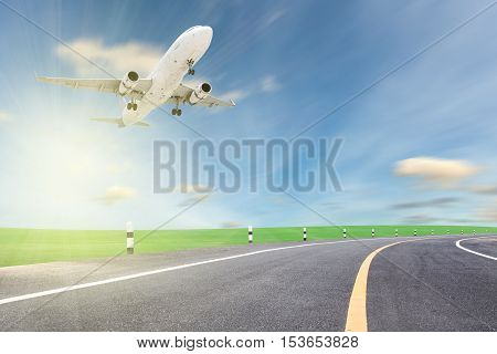 Airplane take off with road curve and beautiful green grass blue sky scenery background open high season travel and tour concept