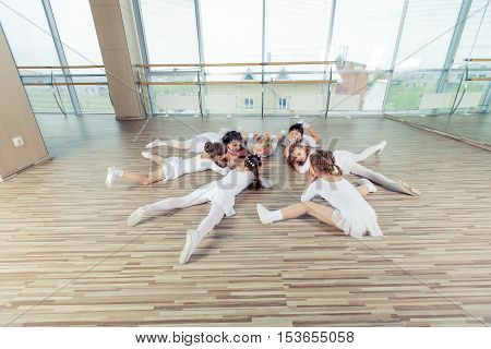 A group of seven little ballerinas sitting on the floor. They are good friend and amazing dance performers
