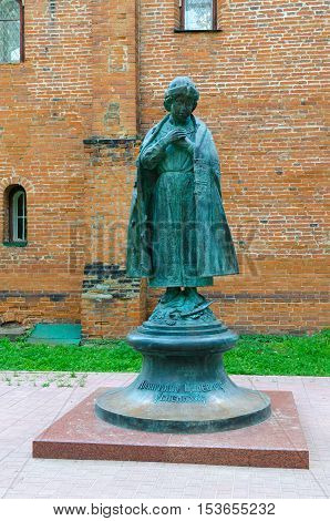 UGLICH RUSSIA - JULY 19 2016: Monument to Tsarevich Dimitry near brick walls of House of Uglich feudal princes in Uglich Kremlin Russia
