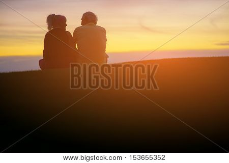 Couple sitting on sky background. Man and woman outdoor. You will never be alone. Live by love and hope.