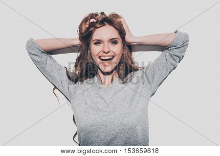 Feeling so happy! Attractive young smiling woman holding hands in hair and looking at camera while standing against grey background