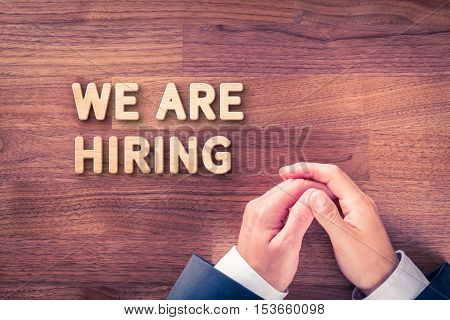 Headhunter (recruiter) and text we are hiring - human resources concept.