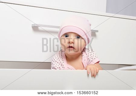 Portrait of a curious baby looking out of the the children's chest of drawers