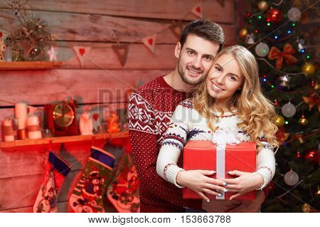 Happy couple with christmas gifts embracing at home. Young blond woman and man in knitted sweaters over christmas tree with copy space