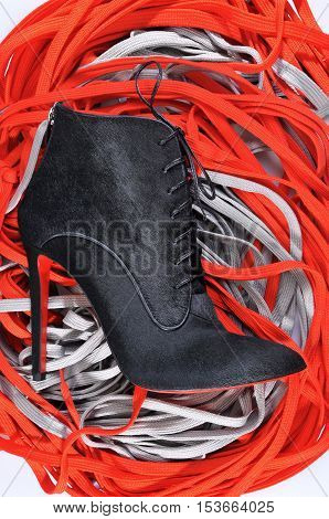 Ukraine Kiev - August 25 2016: Women's boots handmade on a background of colored laces. imitation brand shoes Christian Louboutin showing red soles - illustrative editorial