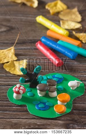 Child Sculpts Plasticine Mushrooms Tree And Autumn Leaves. Consumables For Kids Arts And Crafts On A