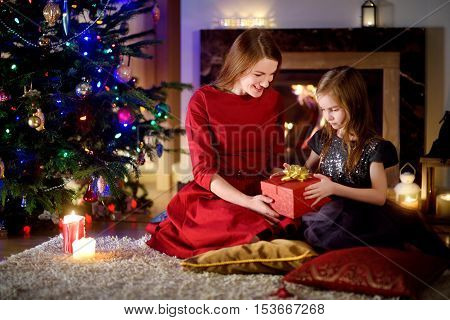 Young mother and her daughter unwrapping Christmas gifts by a fireplace in a cozy dark living room on Christmas eve