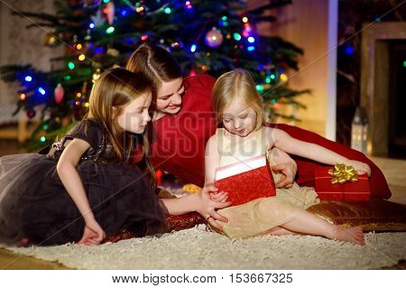 Young Mother And Her Two Daughters Unwrapping Christmas Gifts By A Fireplace