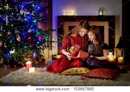 Young Mother And Her Daughter Unwrapping Christmas Gifts By A Fireplace In A Cozy Dark Living Room O