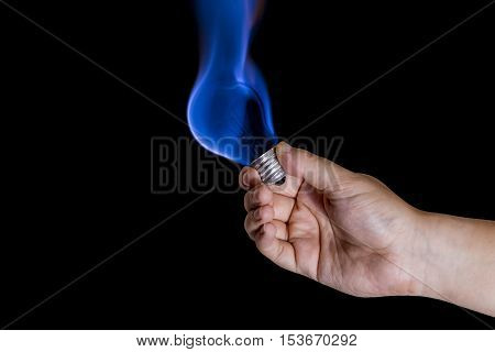 Human hand holding lightbulb burning with blue flame. poster