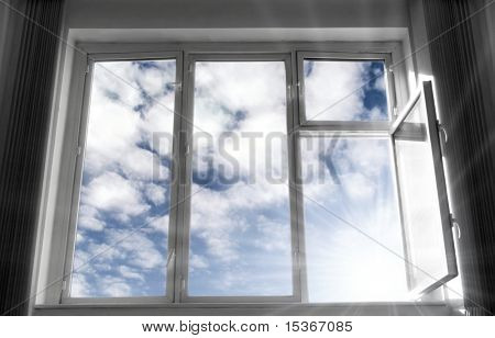 Wide open window. B/w frame, blue sky and bright sunlight. Concept image.