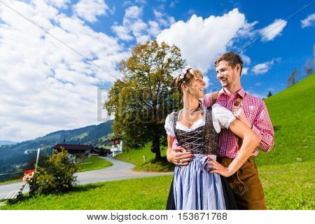 Couple in traditional Tracht standing on meadow in alp mountains