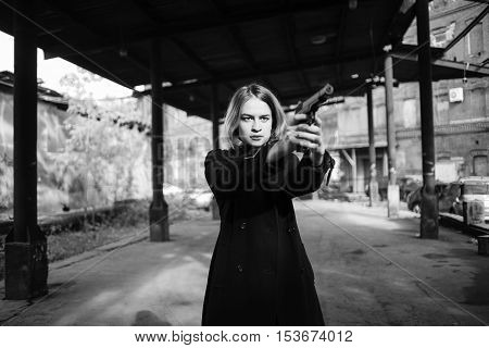 Woman pointing a gun. Girl shooting at someone on the street.