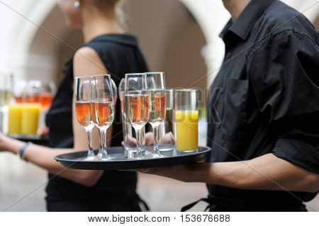 Waiter With Dish Of Wine And Juice Glasses