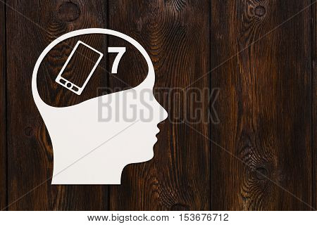 Paper head with smartphone inside. New model mobile phone concept. Abstract conceptual image. Dark wooden background