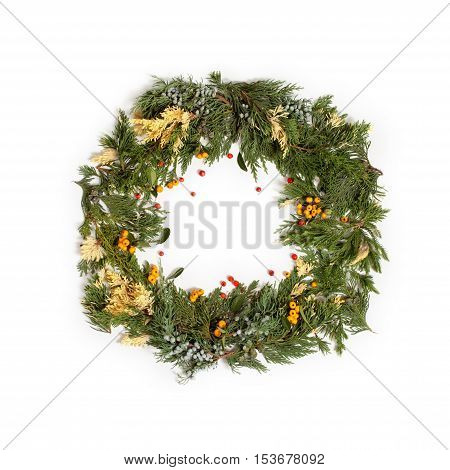 Christmas frame wreath with evergreen fir tree and red and yellow berries isolated on white. Flat lay top view.