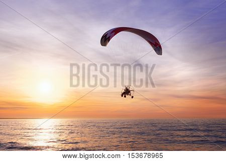 Motor Glider flying over the sea during sunset
