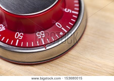 Macro view of a red kitchen egg timer showing 55 minutes on wooden background