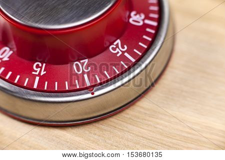Macro view of a red kitchen egg timer showing 20 minutes on wooden background