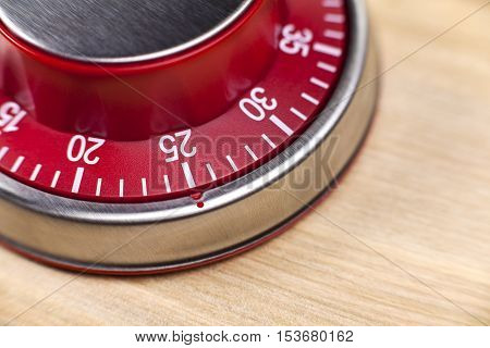 Macro view of a red kitchen egg timer showing 25 minutes on wooden background