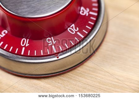 Macro view of a red kitchen egg timer showing 15 minutes on wooden background