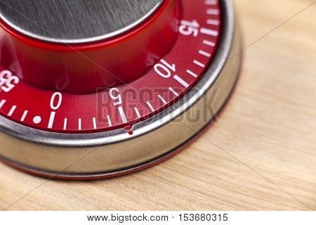 Macro view of a red kitchen egg timer showing 5 minutes on wooden background