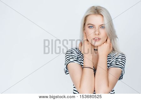 portrait of a beautiful girl with blond hair over light grey background with copy space. Beauty skin tenderness concept