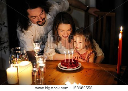 Happy family celebrating their daughter's third birthday