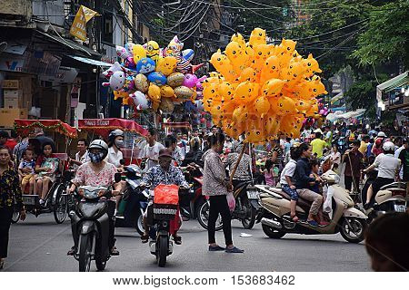 HANOI, VIETNAM, SEPTEMBER 15, 2016 - Unidentified vietnamese crowd of people with motorbikes, shops and balloon vendor on the streets of the busy old quarter in Hanoi, the capital of Vietnam
