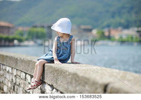 Child Sitting On A Stone Parapet