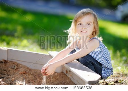 Little Girl Playing In A Sandbox
