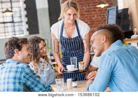 Happy smiling waitress serving food to a young happy group of friends in a cafeteria. Waitress serving on tray coffee to customers. Happy woman serving capuccino to group of multiethnic students.