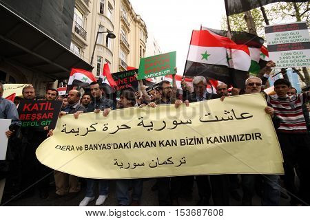 ISTANBUL,TURKEY-DECEMBER 2: Unidentified Syrians living in Istanbul protest the regime of Bashar Essad in front of Syrian Consulate on December 2, 2011 in Istanbul,Turkey.
