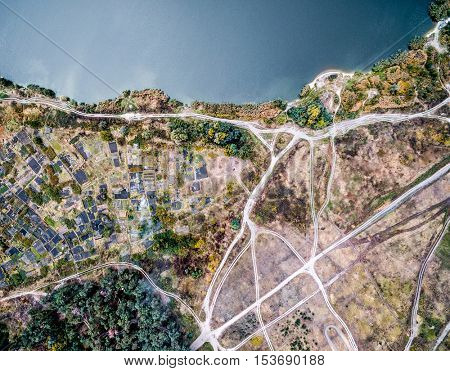 beautiful aerial photo of terrain with rolled roads and tracks on it with access to water