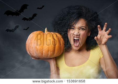 Halloween celebration. Young mixed race african american - caucasian woman holding pumpkin growling at you and gesturing a claw shape with her hands, over gray background with bats and smoke