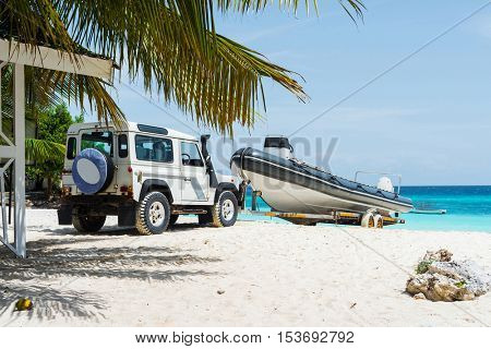 seascape with car transporting motorboat on african sandy beach