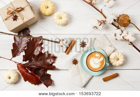 Pumpkin spice latte. Coffee cup with foam, cinnamon sticks, red oak leaves and small yellow pumpkins at white wood background. Autumn fall hot drinks, cafe and bar concept, top view with copy space