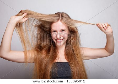 hair care hairstyle and people concept - young woman or teenage girl holding strand of her hair. brunette with long hair smiling at the camera.