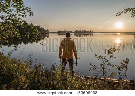 Man is fishing on the sunset lake