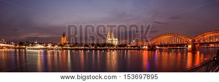 Illuminated Cologne Cathedral and bridge at night in Cologne, panoramic view