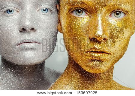 Beautiful amazing portrait of two woman. Unreal make up like a space. Closeup shooting in studio with silver background. Emotion posing of model. gold silver glitter.