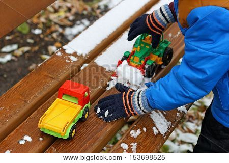 Part of the image of a small child who is standing near a wooden bench covered with snow. The child clears snow from a bench using a toy excavator and toy cars.